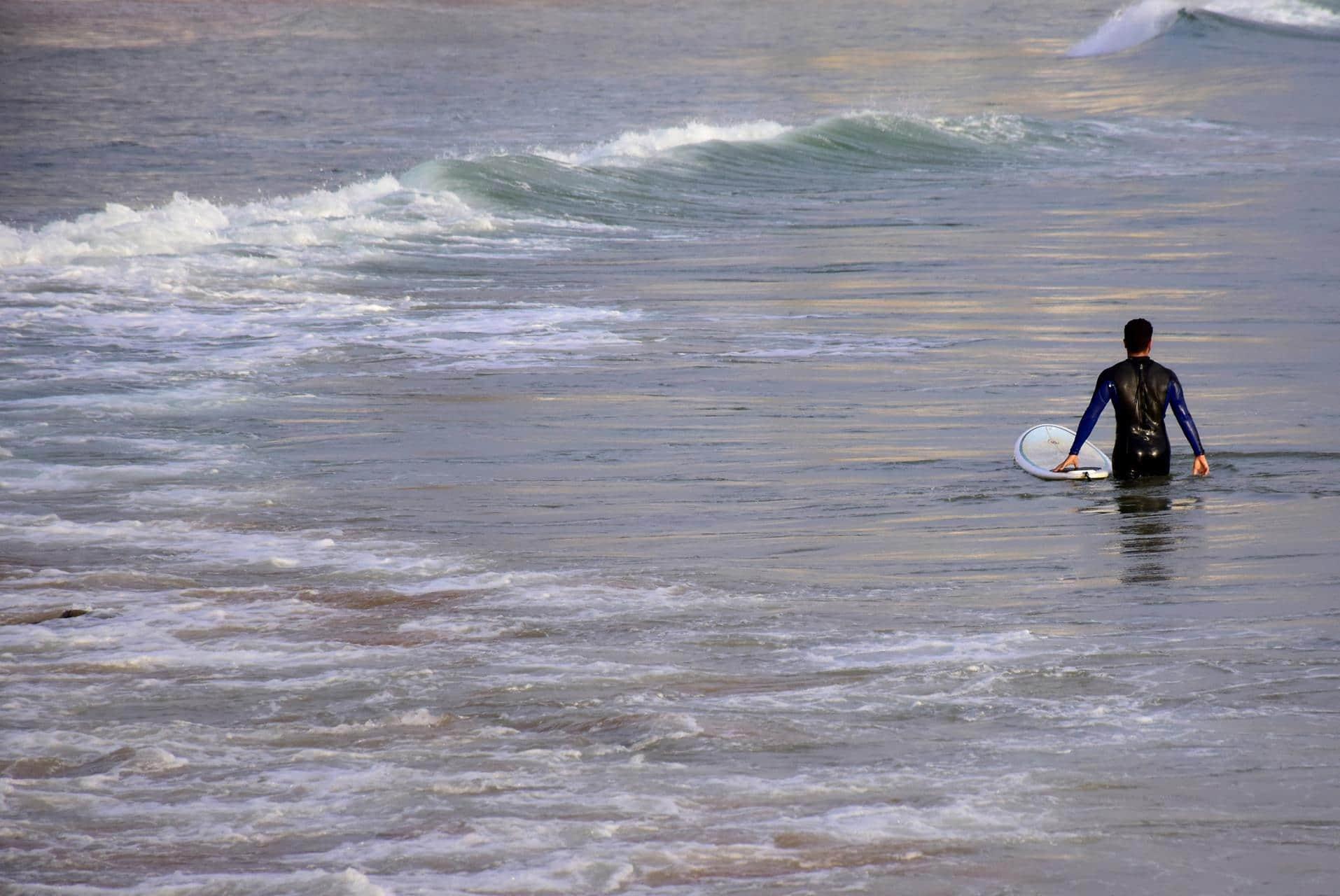 preparing to surf in blue waves