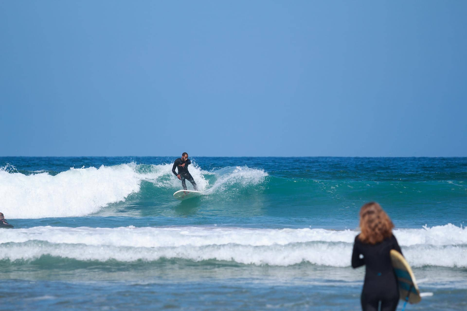 couple surfing waves in blue waves